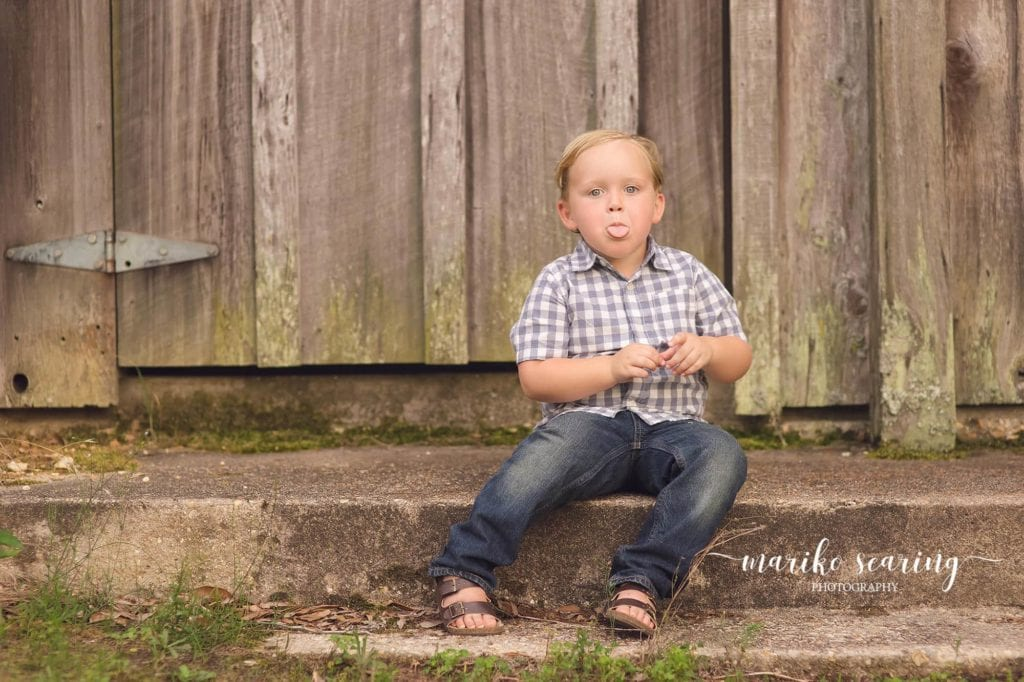boy sitting in front of barn sticking tounge out by Baton Rouge Photographer