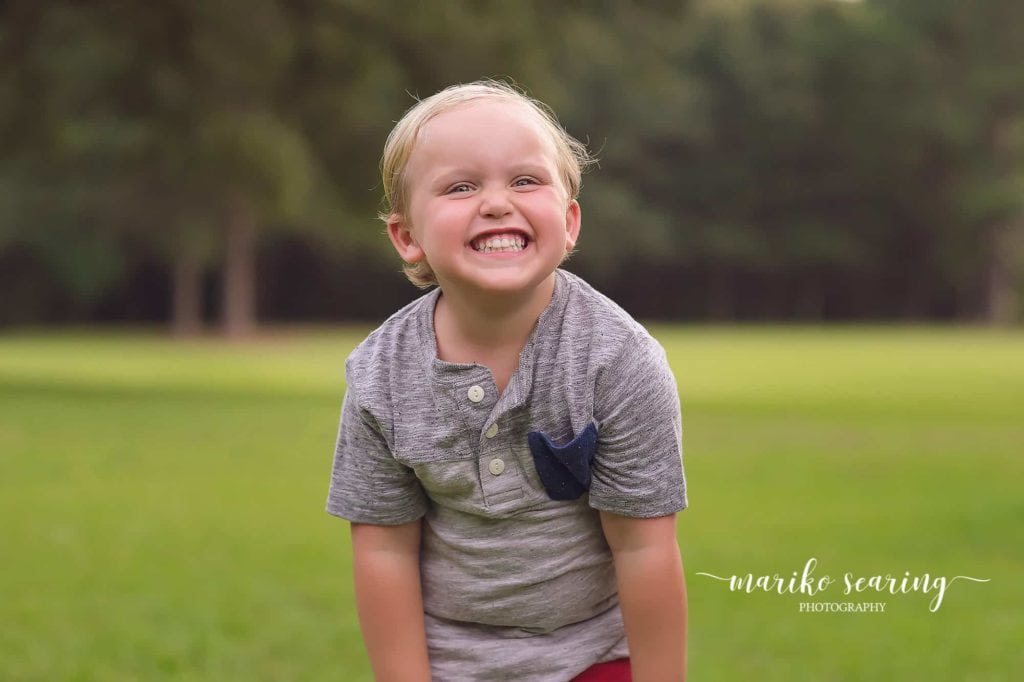 boy standing in field laughing by Baton Rouge photographer
