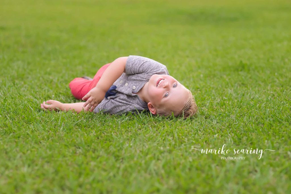 boy rolling in field laughing by Baton Rouge Photographer