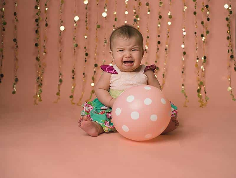 baby crying with ballon in a studio by baby photographer Baton Rouge, LA