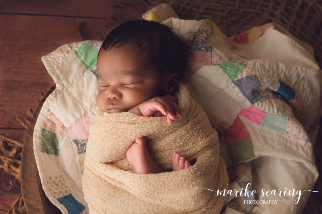 wrapped baby on quilt in Baton Rouge by newborn photographer
