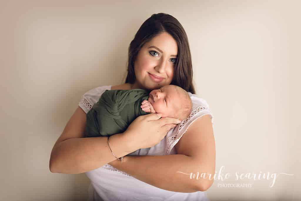 mom holding wrapped baby in studio in Baton Rouge by newborn photographer