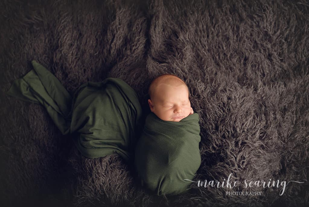 wrapped baby on fur bu newborn photographer in Baton Rouge