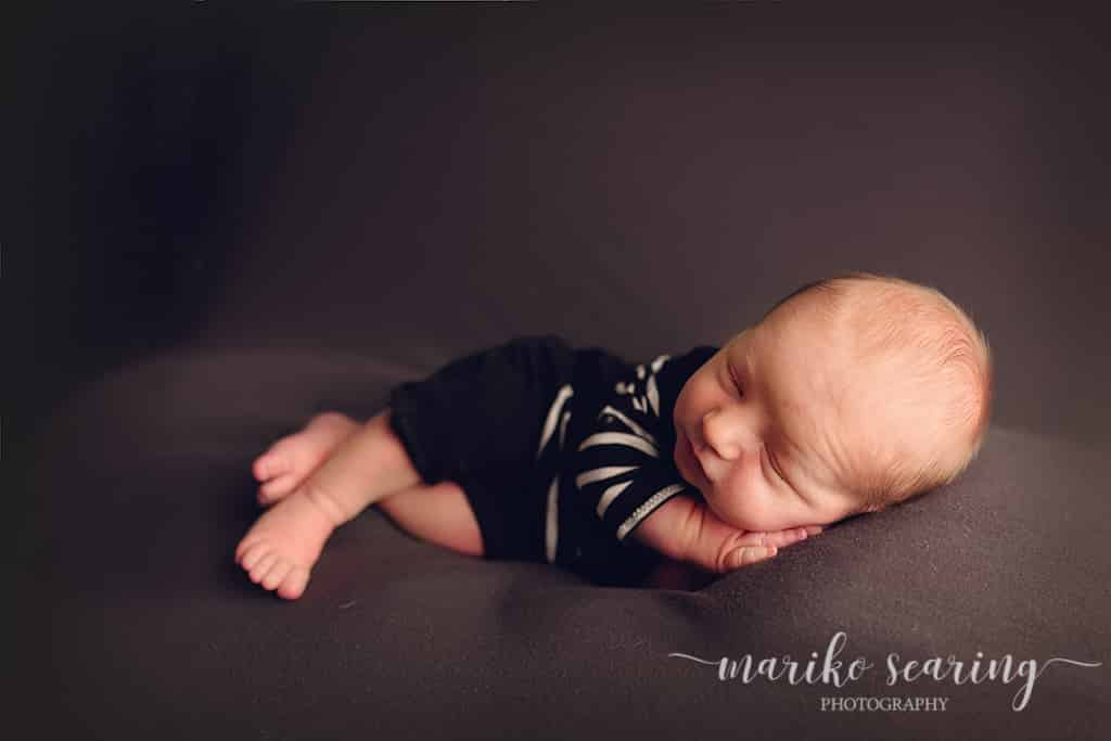 posed baby lying on side by newborn photographer in Baton Rouge
