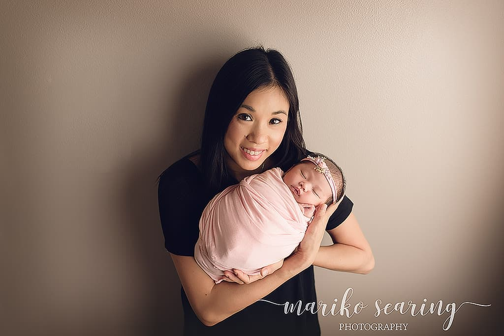 wrapped baby in mother's arm by newborn photographer in Baton Rouge
