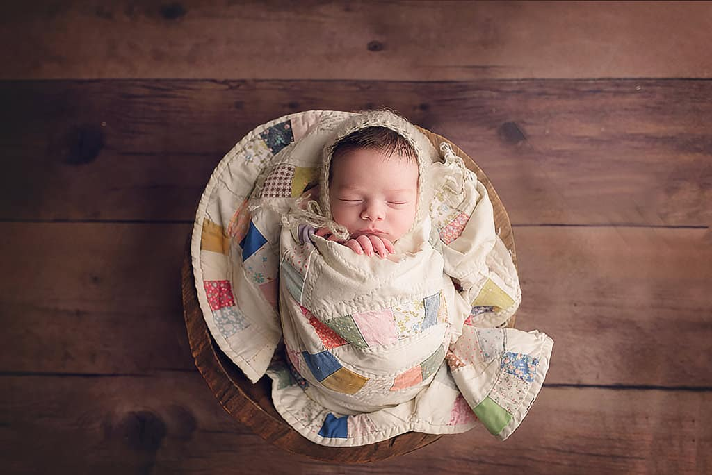 wrapped newborn in bowl with quilt and bonnet by newborn photographer in Baton Rouge