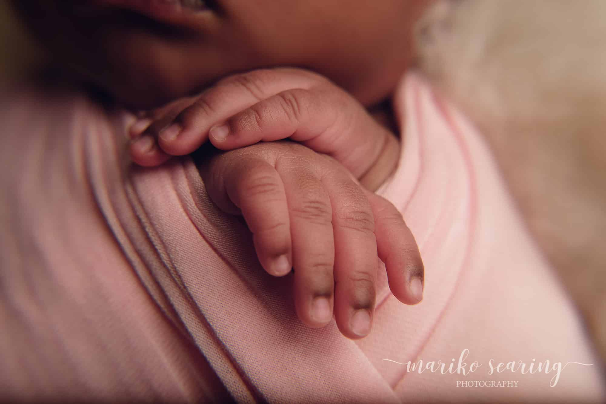 denham springs posed newborn photographer baby wrapped in pink hand close up