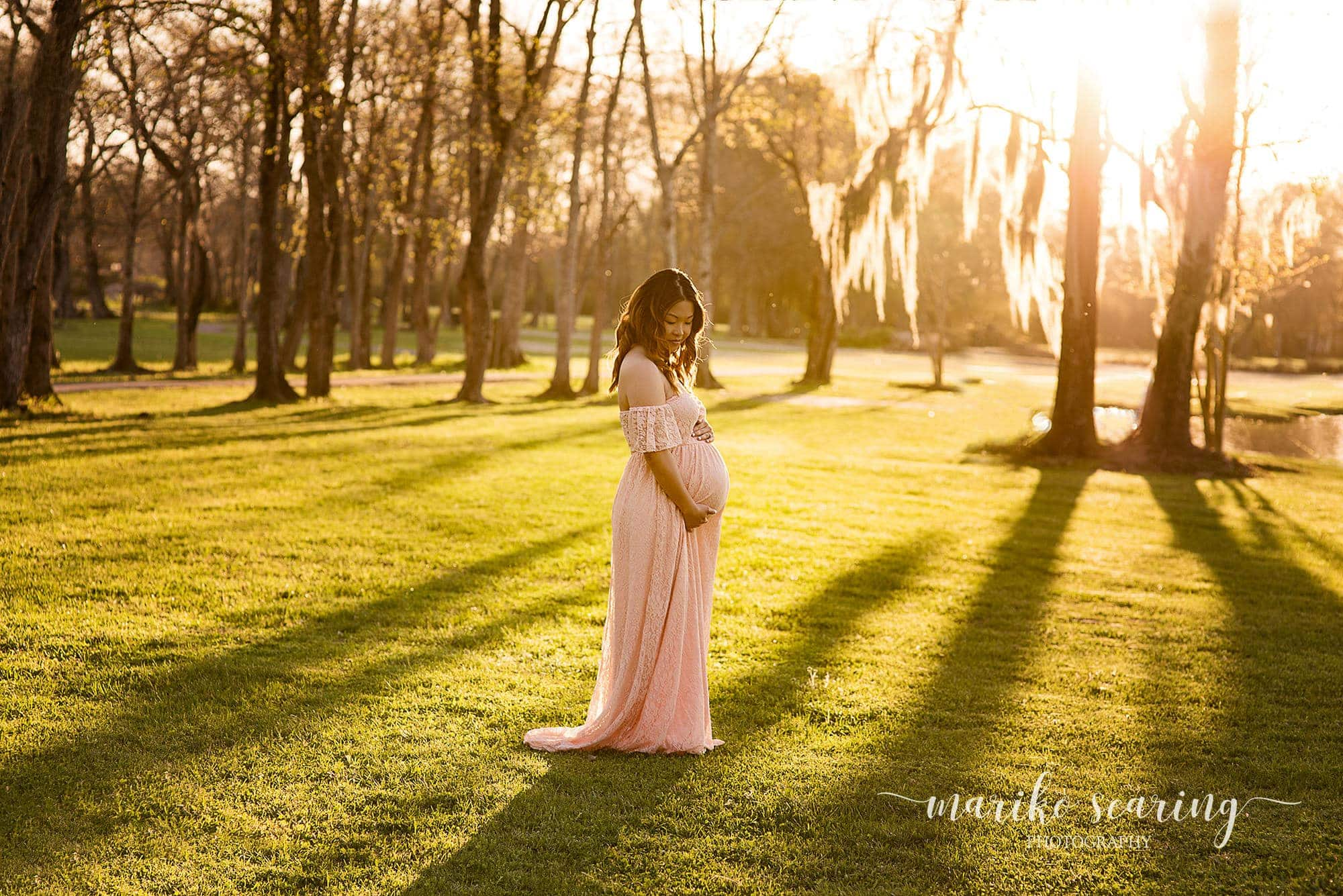 Baton Rouge maternity newborn photographer mother in pink dress in the park