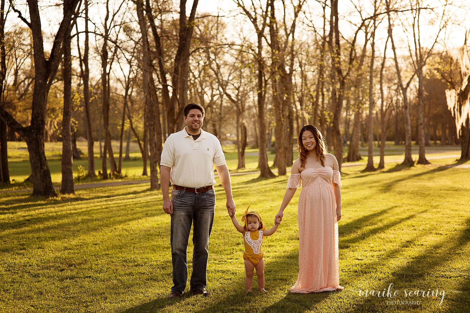 Baton Rouge maternity newborn photographer mariko searing photography maternity pregnant woman holding hands with daughter and husband in the park