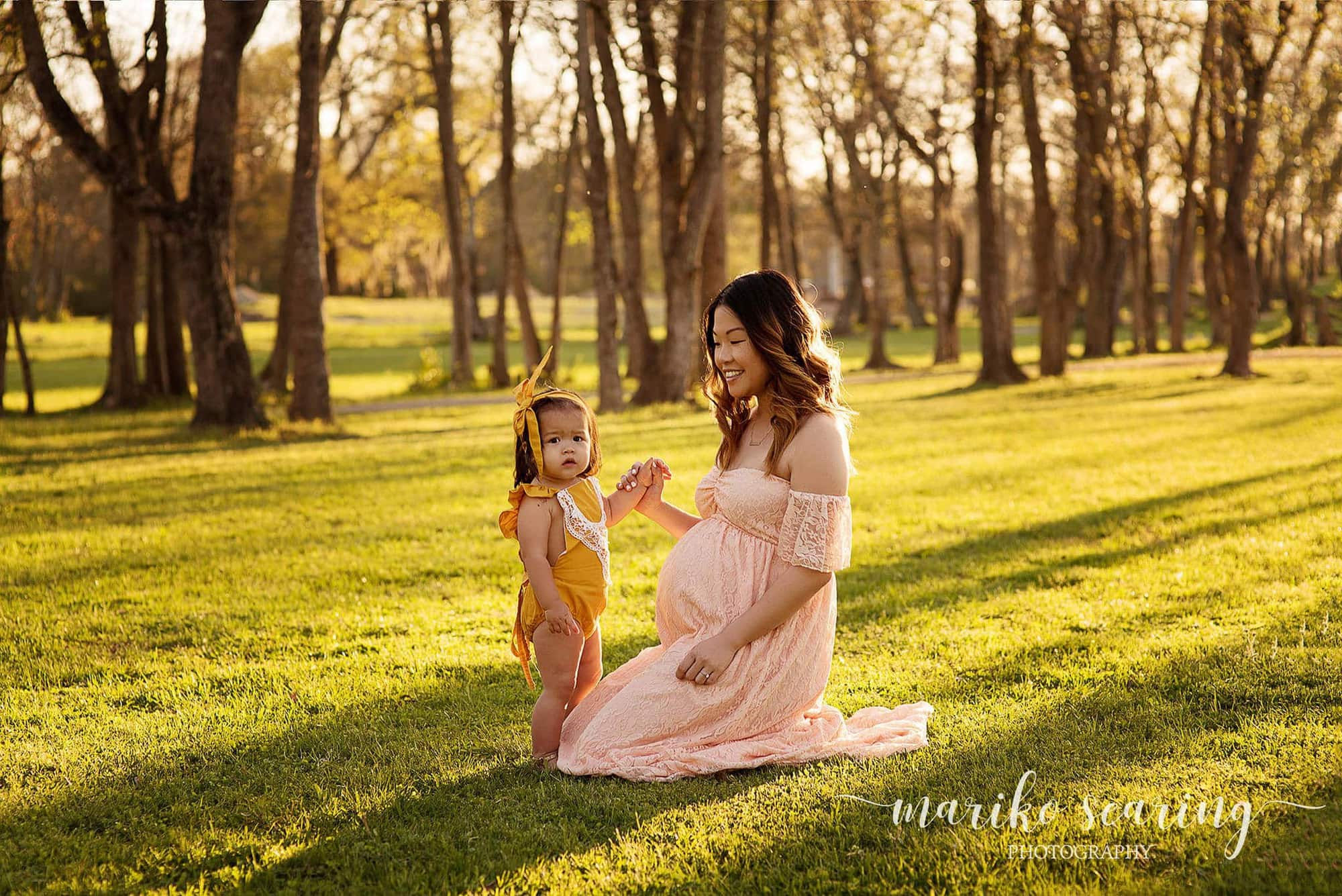 Baton Rouge maternity newborn photographer mariko searing photography maternity pregnant woman sitting with daughter in the park