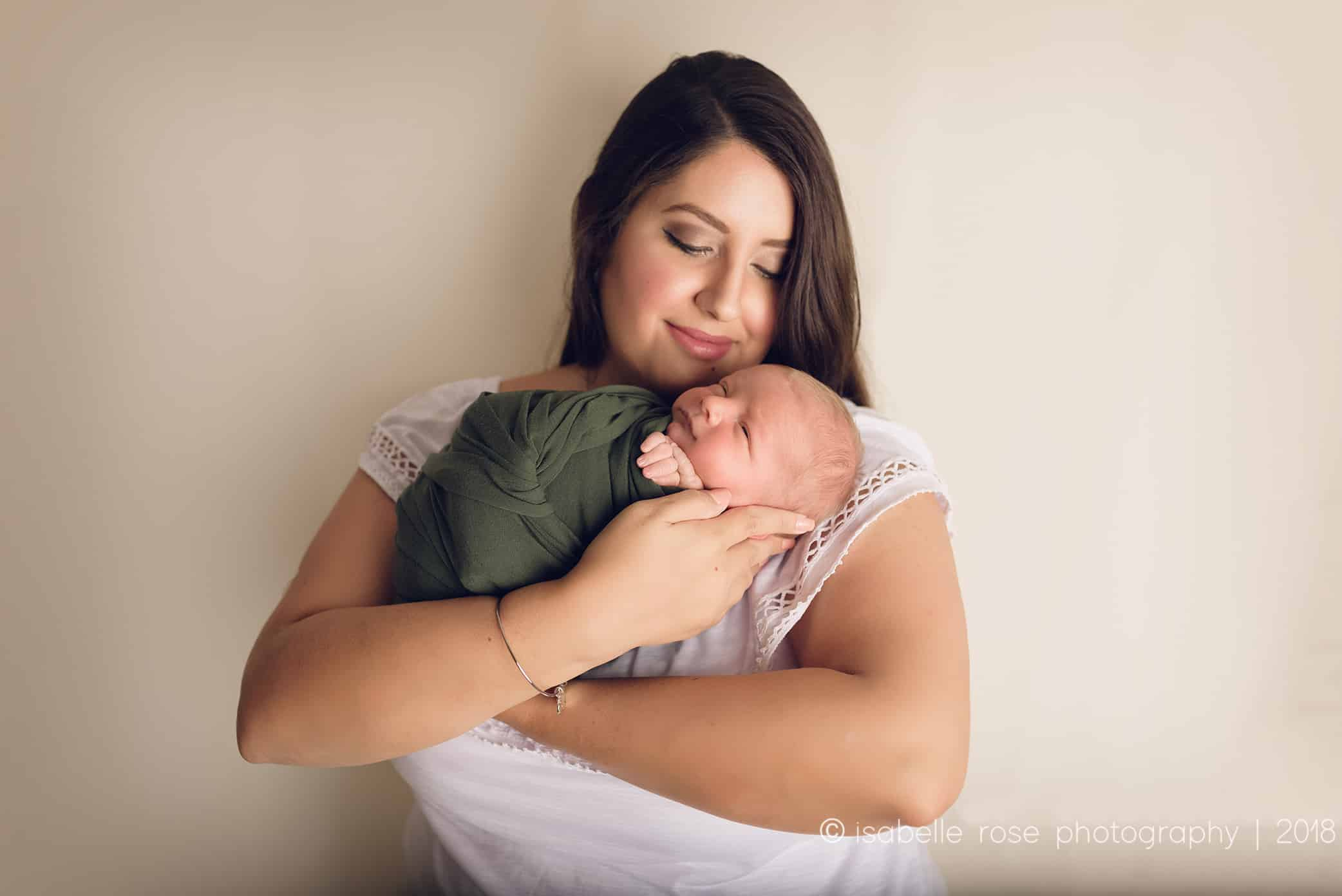 07302018 posed newborn photographer in baton rouge mother holding wrapped baby in blue