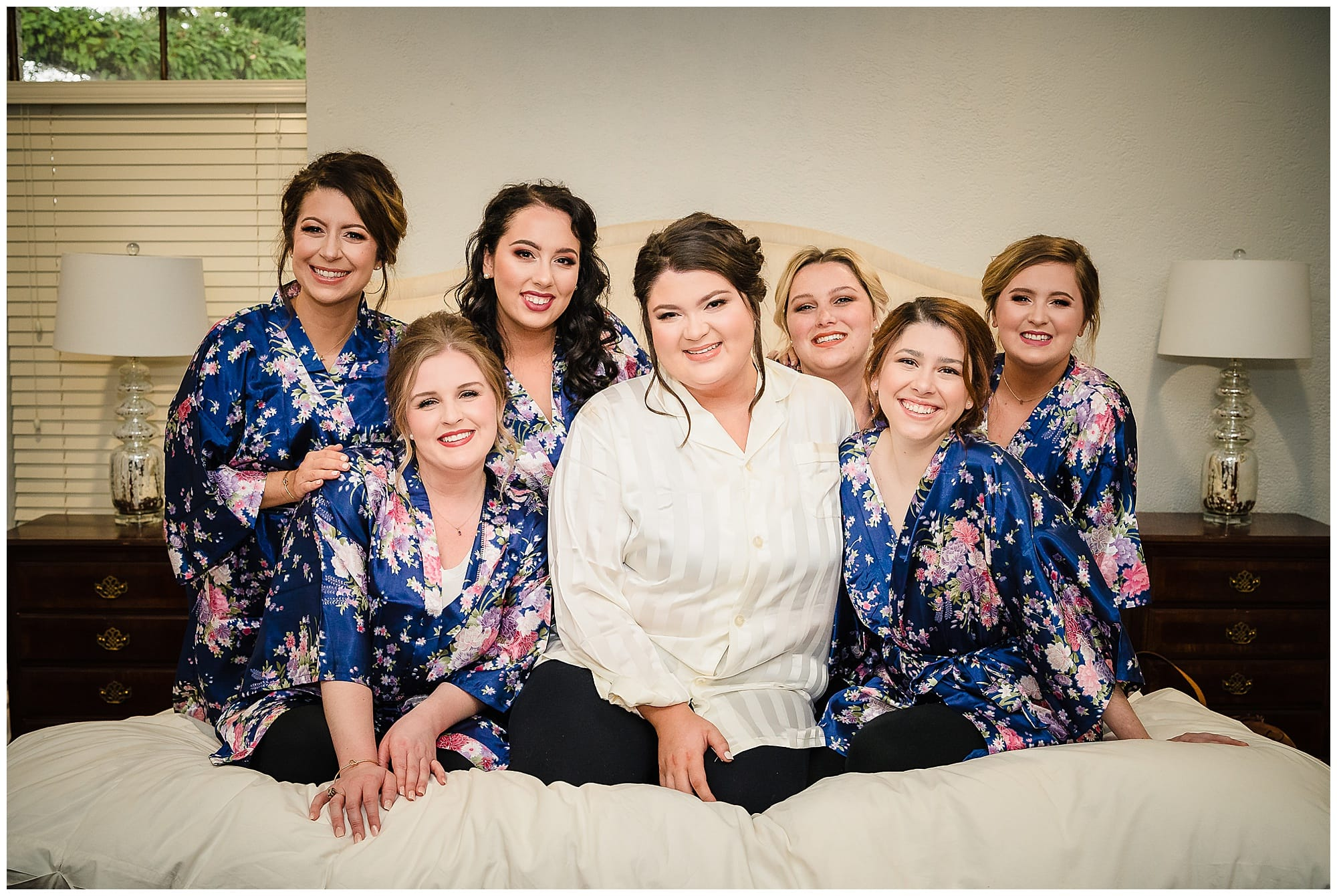 bridal party posing on bed with matching robes