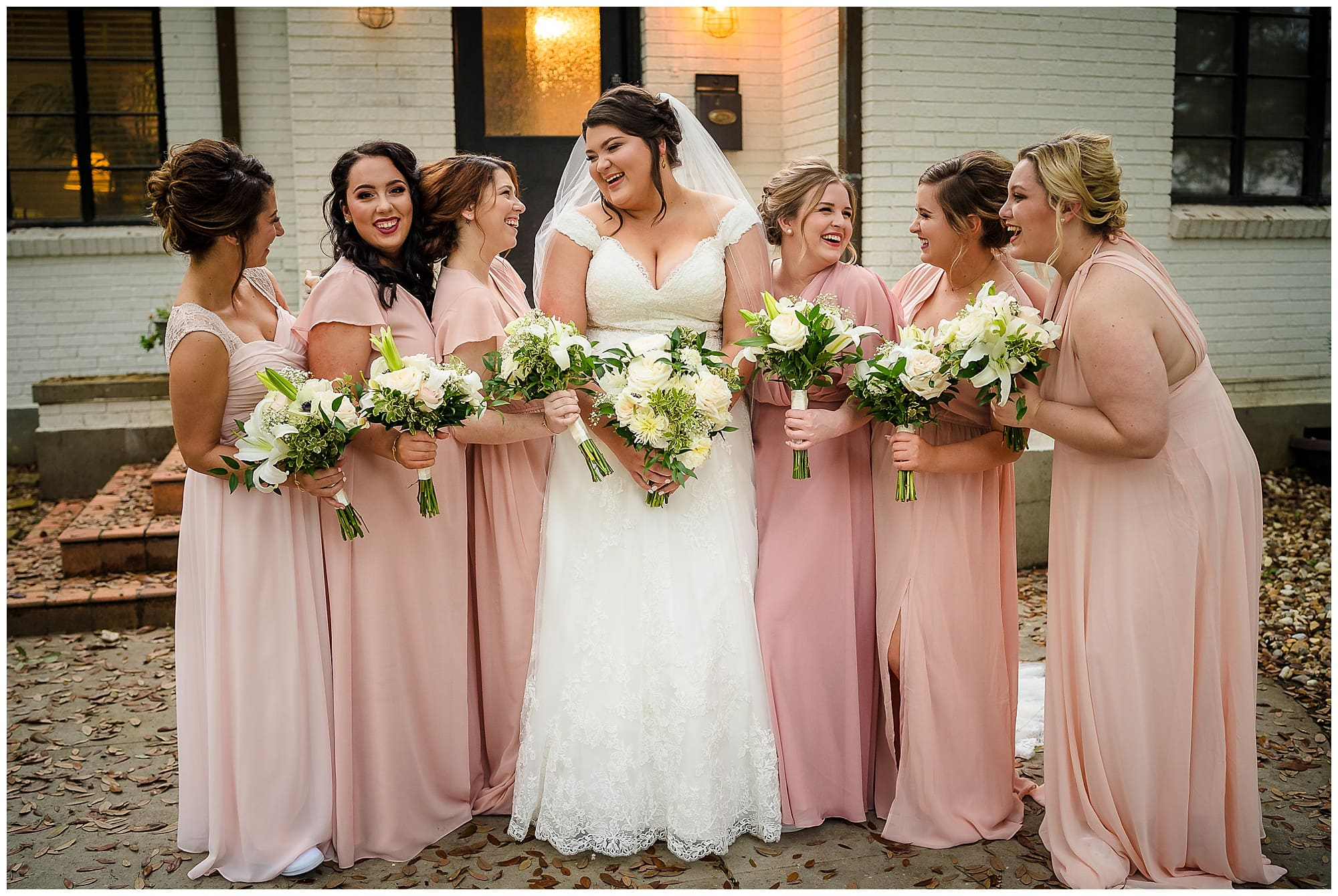 bride and bridesmaids laughing in front of house