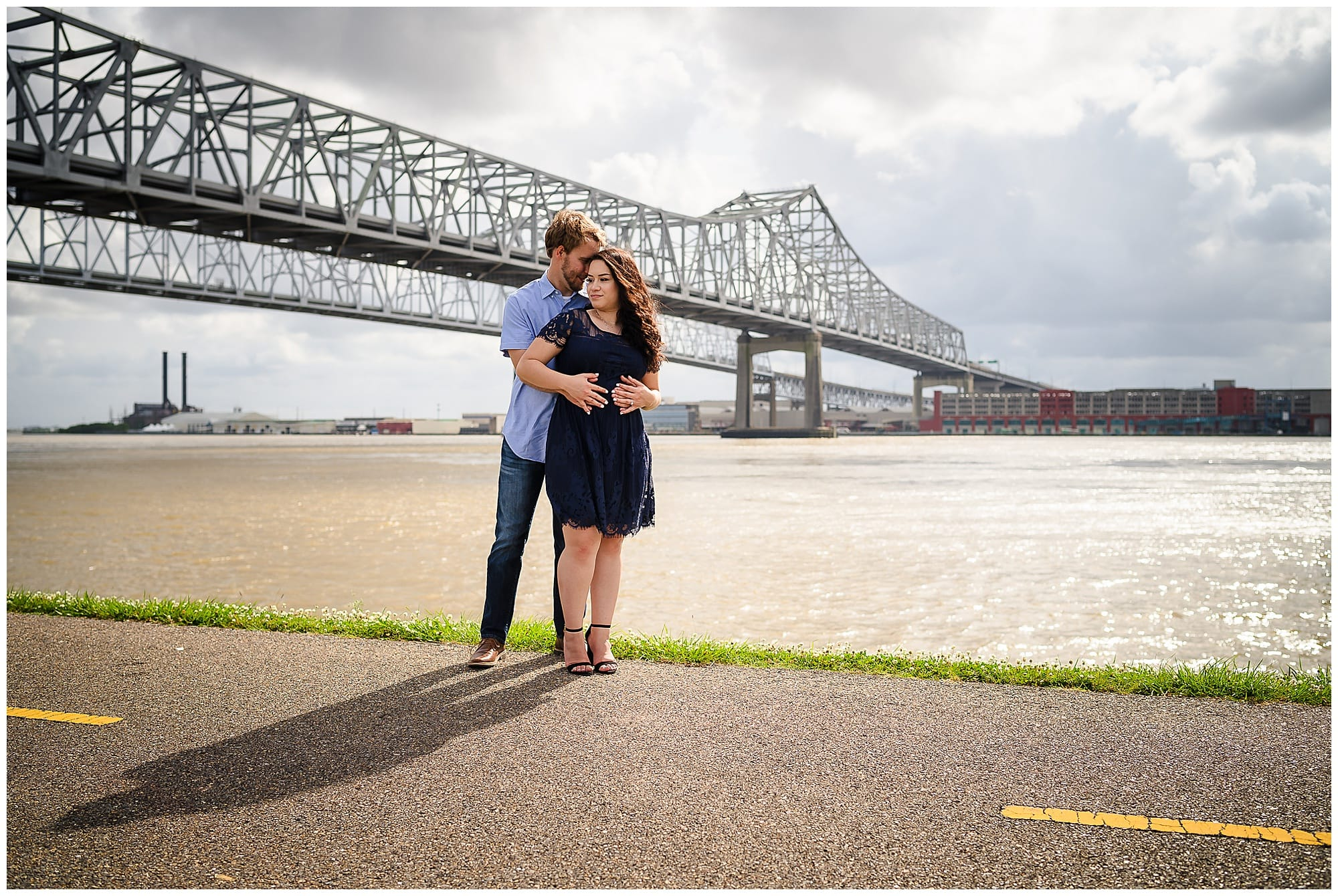 couple posing in front of bridge in downtown New Orleans