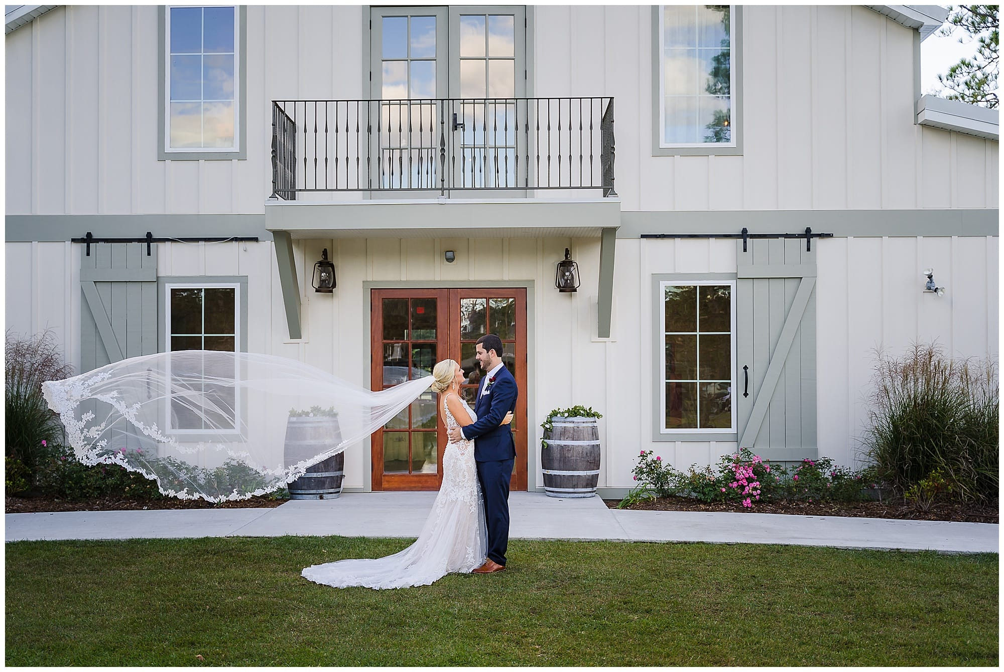 The Sadie Jane Wedding Venue bridal couple holding each other veil flying