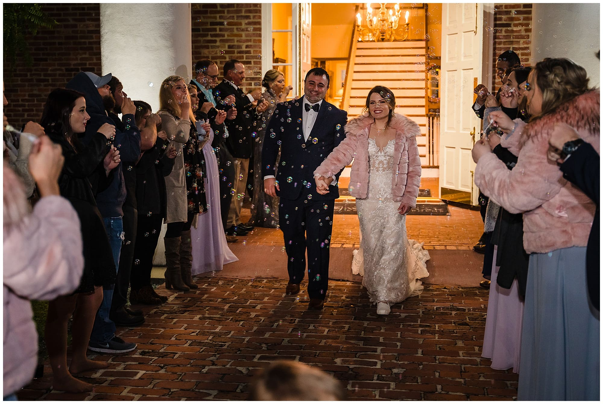 bride and groom exit while guests blow bubbles