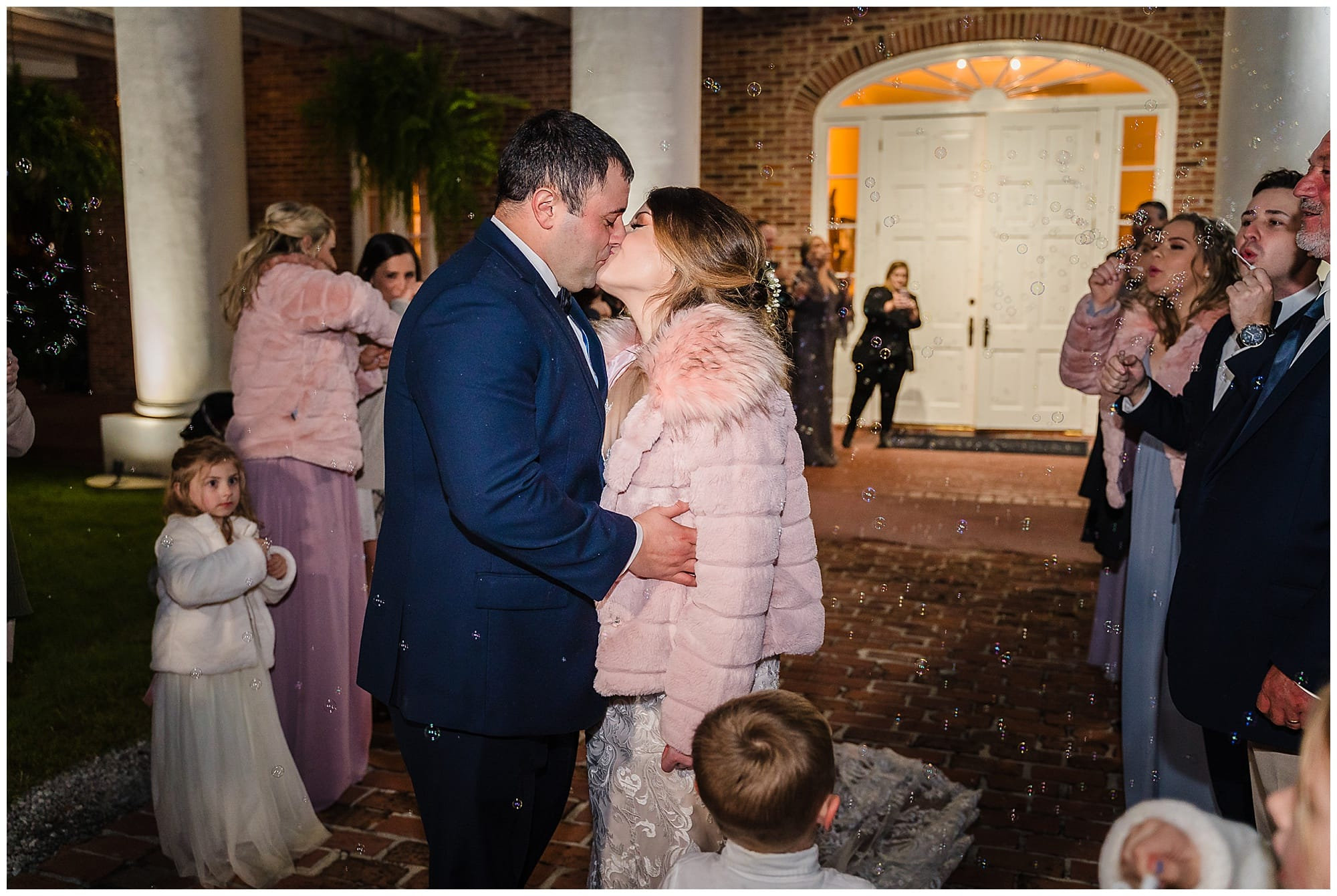 bride and groom kiss while guests blow bubbles