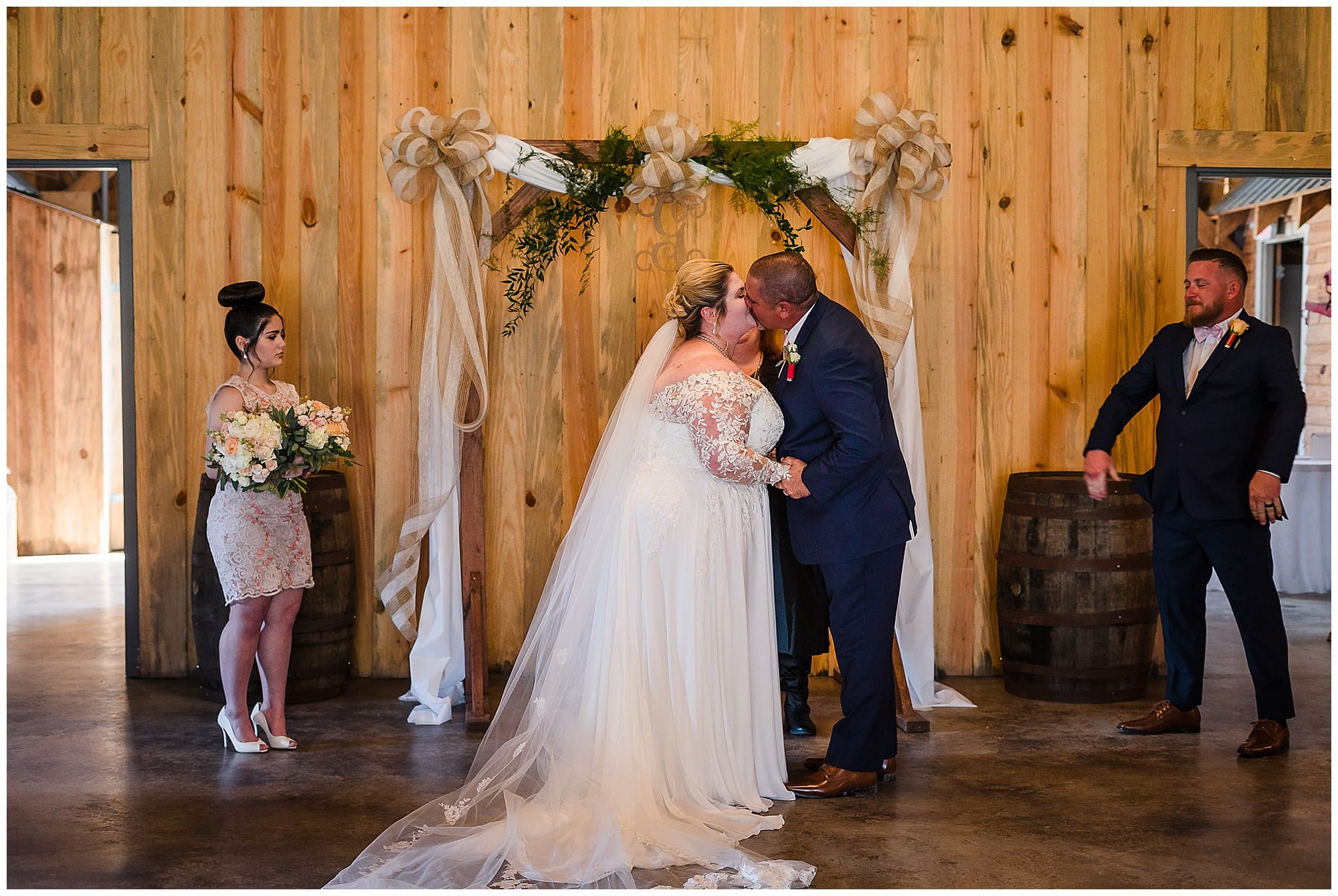 The Barn at TH Farm wedding ceremony fist kiss