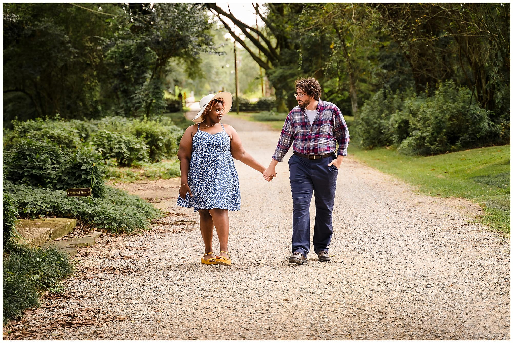 couple holing hands and walking in Windrush Gardens Baton Rouge engagement session