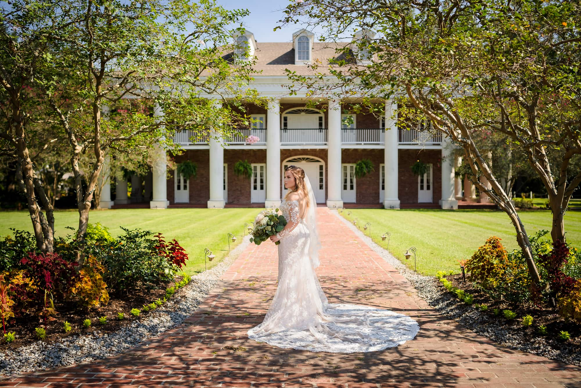 bride in front of white oak estate